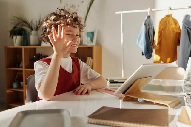 photo-of-child-smiling-while-using-tablet-computer-4145032